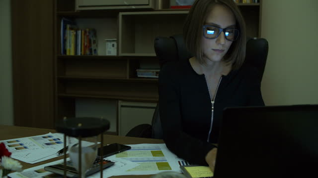 4K:Businesswoman working late at night in her office and looking at the monitor.