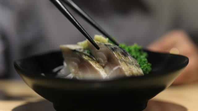 vídeos de stock e filmes b-roll de 4k:close up chopstick pick up salmon sashimi japan food - pauzinhos