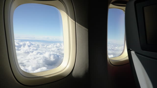 4k:clouds outside airplane window - vehicle interior stock videos & royalty-free footage