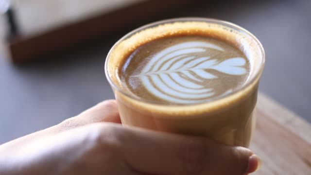 4K: kaffe med konst latte på bordet av Coffee Shop