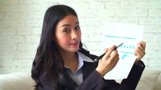 4K:Confident young woman in formalwear pointing data on paper graph during mobile conference.