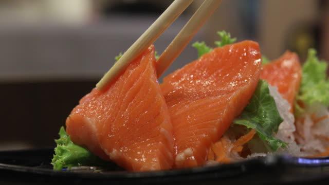 4k:eating salmon sashimi japan food - sashimi stock videos & royalty-free footage