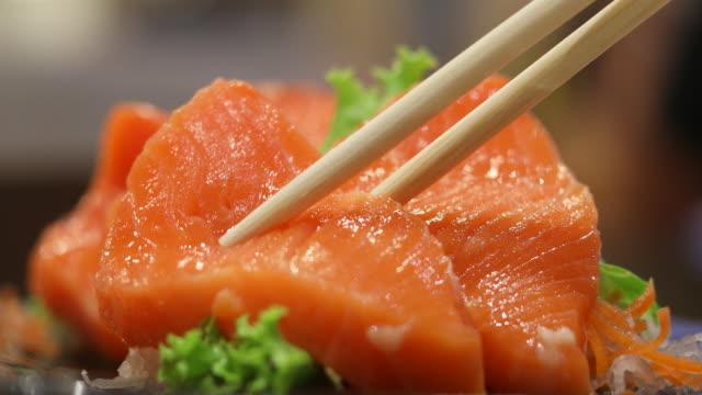 vídeos de stock, filmes e b-roll de 4k: comer salmão sashimi japão comida - sashimi