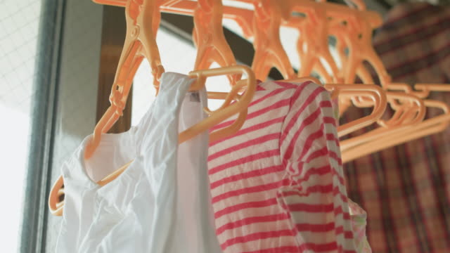 4K,hanging clothes to dry indoors on a rainy day.