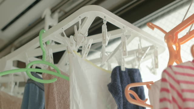 4k,hanging clothes to dry indoors on a rainy day. - washing stock videos & royalty-free footage