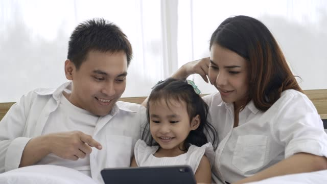 4k,happy asian family playing tablet on the bed in white bedroom and jump on the bed,family concept. - graphics tablet stock videos & royalty-free footage