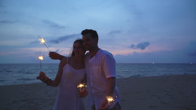 4K:Happy couple lovers lighting sparklers and enjoying freedom at beach during sunset.