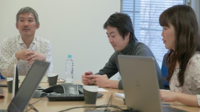 4k,japanese businessmen and businesswomen having a meeting. - コンピュータ機器点の映像素材/bロール