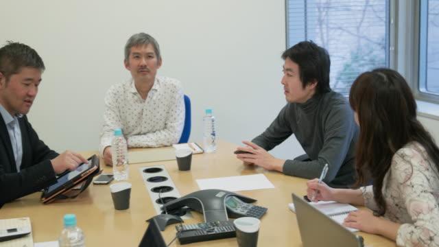 4k,japanese businessmen and businesswomen having a meeting. - ホワイトカラー点の映像素材/bロール