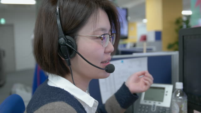 4k,japanese woman with head phones talking to customers. - brille stock-videos und b-roll-filmmaterial