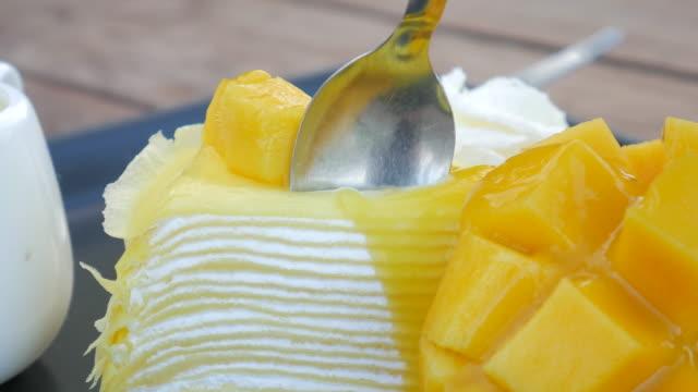 4k:mango cake eating mango cheese cake on plate with fresh fruit decoration - mango stock videos and b-roll footage