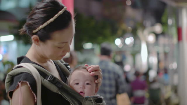 4k,mother and baby on the street at night. - baby carrier stock videos & royalty-free footage