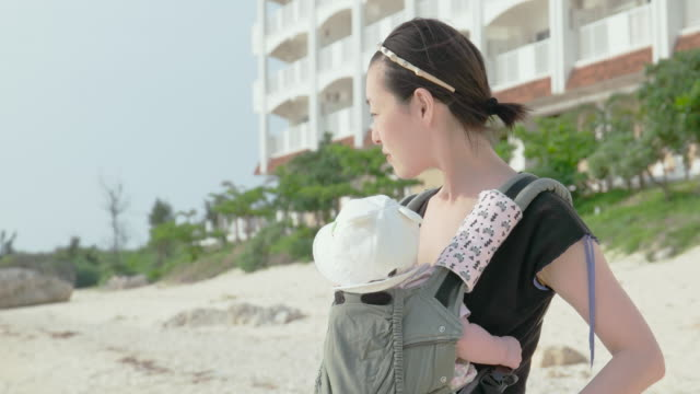 4K,Mother and baby walking on beach.
