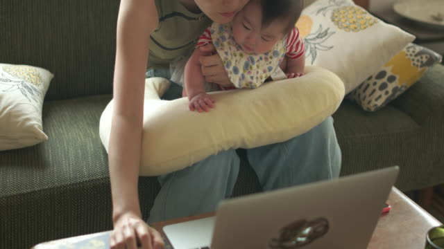 4K,Mother using laptop with baby.