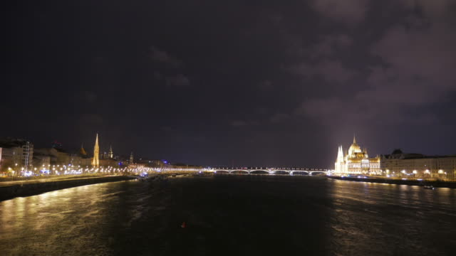 vídeos de stock e filmes b-roll de 4 k: parlamento budapest hungria e rio danúbio à noite - ponte széchenyi lánchíd