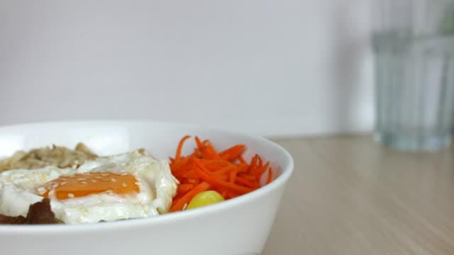 4 k  : に注ぎます。トマトソースのビビンバ、韓国料理 - 玄米点の映像素材/bロール