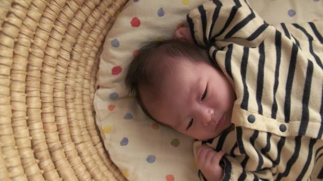 4k,selective focus shot of japanese newborn baby. - babygro stock videos & royalty-free footage
