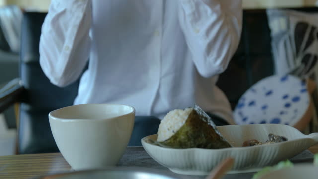 "4k,selective focus, young female eating ""onigiri"" at cafe. - テーブル点の映像素材/bロール"