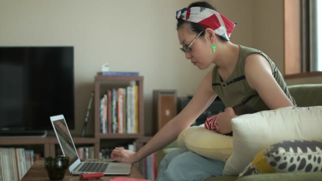 4k,side view of mother using laptop with baby sleeps on mother's knees. - 体の動き点の映像素材/bロール