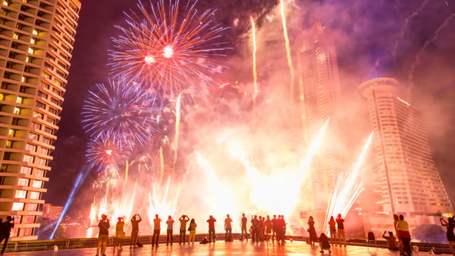 4KTime-lapse colorful fireworks with peoples on rooftop Chao Phraya river with landmark building in Bangkok