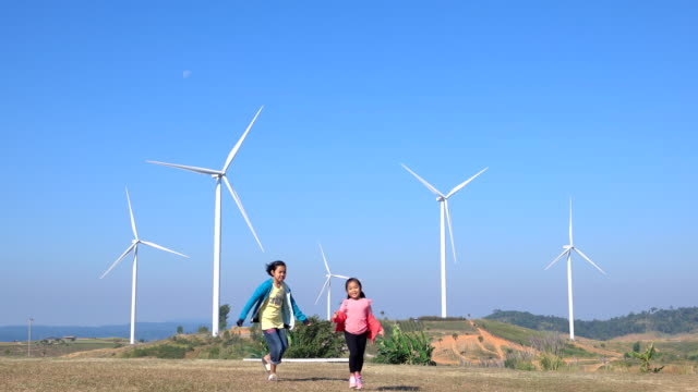 4k:two mädchen spielen im windpark turbinen am morgen - fuel and power generation stock-videos und b-roll-filmmaterial