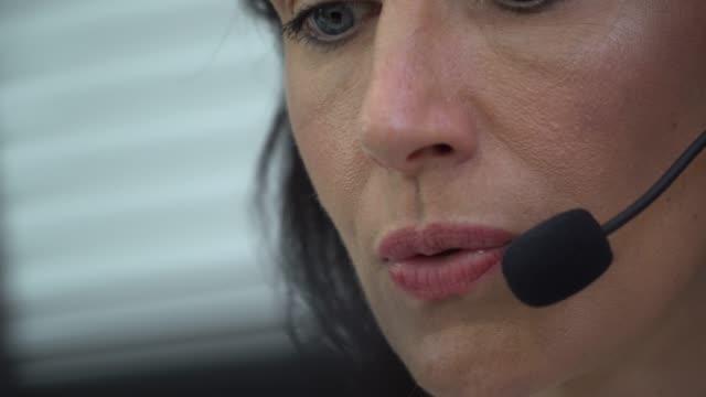 4k:woman arbeitet in einem call-center mit einem kopfhörer - callcenter stock-videos und b-roll-filmmaterial