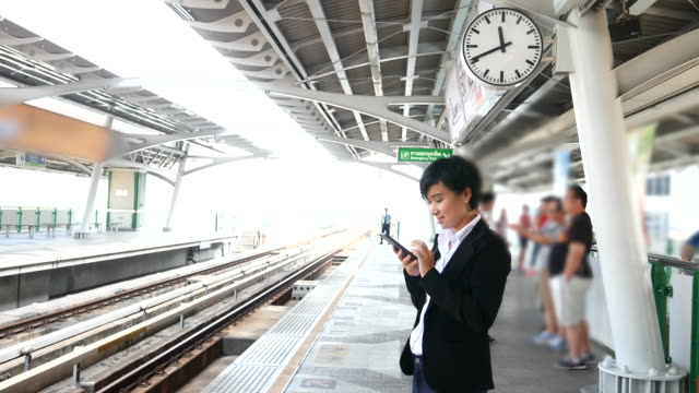 4k:women waiting the train and using smart phone. - railway station stock videos and b-roll footage