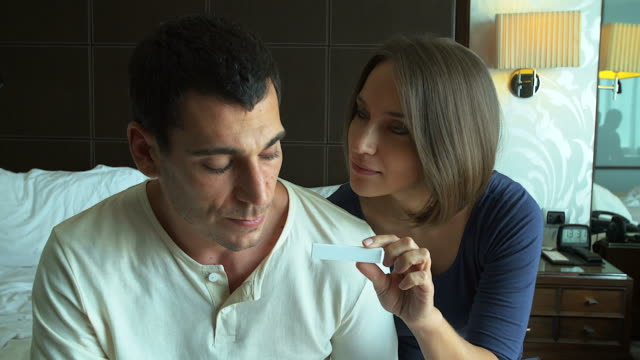 4K:Worried couple finding out results of a pregnancy test in the bedroom.