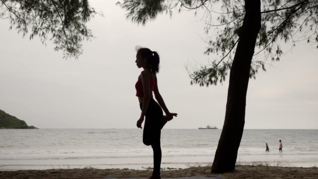 vídeos de stock, filmes e b-roll de 4k/pose magro asiático novo da ioga da mulher na praia no por do sol, fundo do nascer do sol. aptidão, esporte, ioga, silhueta, e conceito saudável. - braço humano