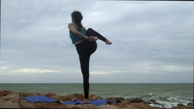 vídeos de stock, filmes e b-roll de 4k/pose magro asiático novo da ioga da mulher na praia no por do sol, fundo do nascer do sol. aptidão, esporte, ioga e conceito saudável. - braço humano