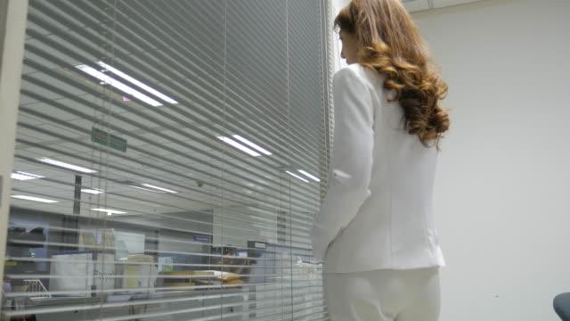 4 K :  junge Geschäftsfrau sieht über Jalousien aus Ihrem Büro