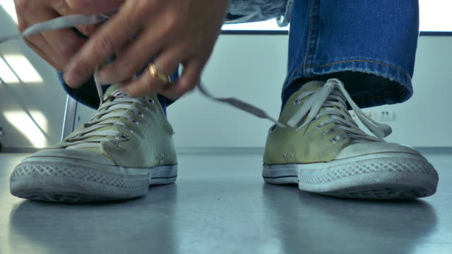 4k:Young Men tying shoelaces