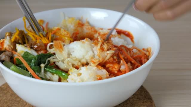 vídeos y material grabado en eventos de stock de 4 k :  mujer joven comiendo bi bim bap, comida coreana - comida coreana