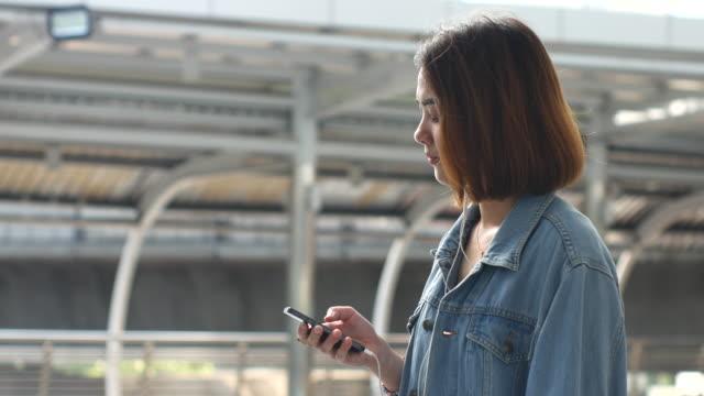 vídeos de stock e filmes b-roll de 4 k: jovem mulher ouvir música em espera para o comboio - barba por fazer