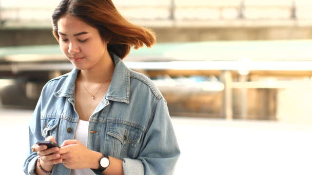 4K:Young woman using smart phone