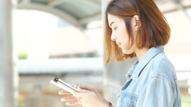 4 k :  junge frau mit tablet auf der sky-train-bahnhof - kopf nach hinten stock-videos und b-roll-filmmaterial