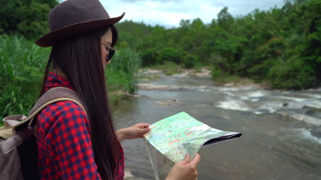 4K:Young women looking a map on her adventure trip.