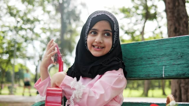 4l/slow motion ,asian islam girl playing guitar or ukulele  in the public park on weekend holiday. - hijab stock videos & royalty-free footage