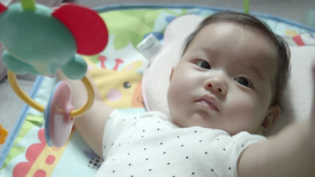 A 4month baby girl playing with her Toys at home