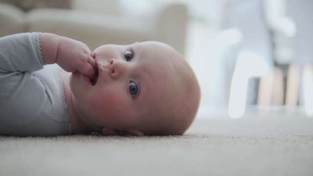 a 4-month old blue-eyed baby boy relaxing on the floor - sucking stock videos & royalty-free footage