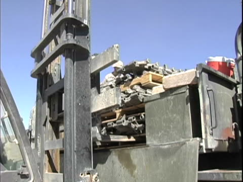 4th may 2005 montage civilian contactor using forklift soldiers removing turret gun and loading tires at supply yard / fob speicher iraq / audio - one mid adult woman only stock videos & royalty-free footage