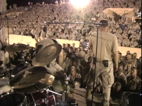vídeos de stock e filmes b-roll de 4th may 2005 montage concert at fob speicher held in bombed out soccer stadium, army rock band, cheering soldiers / fob speicher, iraq / audio - rocking