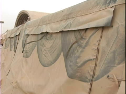 4th may 2005 montage dust storm aftermath, tent tassels blowing in wind, living area, dust covered water bottles / fob speicher, iraq / audio - one mid adult man only stock videos & royalty-free footage