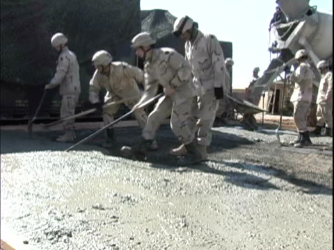 4th may 2005 montage soldiers pouring and finishing concrete for new construction project / fob speicher, iraq / audio - 30代の男性だけ点の映像素材/bロール