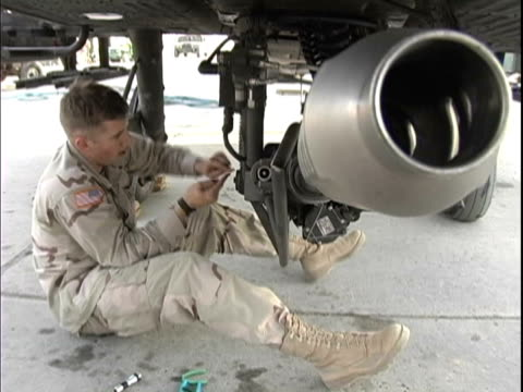 4th may 2005 montage us soldier working on 30mm belly gun on ah64 apache with rocket tubes and hellfire missiles / fob speicher, iraq / audio - one mid adult man only stock videos & royalty-free footage