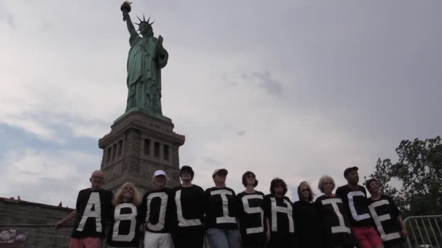 4th of july rise and resist activists including therese patricia okoumou who would later climb the statue, hanging banner 'abolish ice' from the... - freiheitsstatue stock-videos und b-roll-filmmaterial