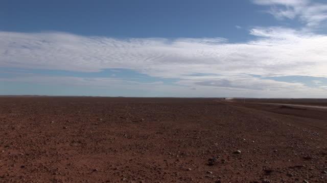 ws 4x4 driving on road crossing simpson desert, northern territory, australia - öde landschaft stock-videos und b-roll-filmmaterial