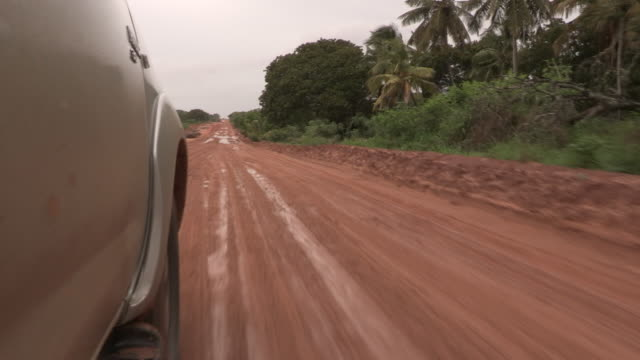a 4x4 travels along a muddy earth road, mozambique - audio available stock videos & royalty-free footage