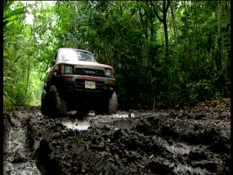 4x4 travels through thick mud in rainforest Guatemala