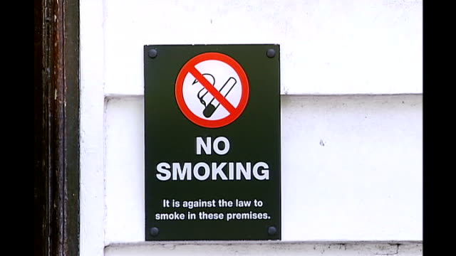 50th anniverary of link between smoking and cancer / campaigners call for widening of smoking ban; anonymous shot of smokers ext 'no smoking' sign on... - no smoking sign stock videos & royalty-free footage